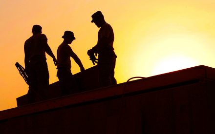 silhouette of workers in front of a setting sun