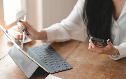 Woman holding phone and working with pen on iPad