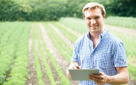 man holding a notebook in front of a field