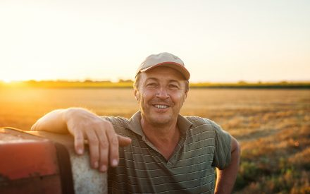 farmer smiling in front of his field