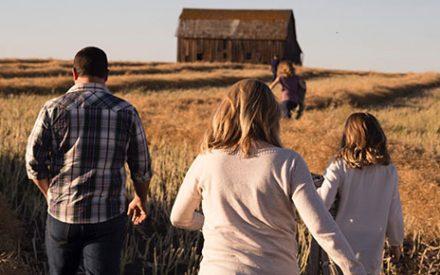 Man, woman and three children walking in a field toward a barn.