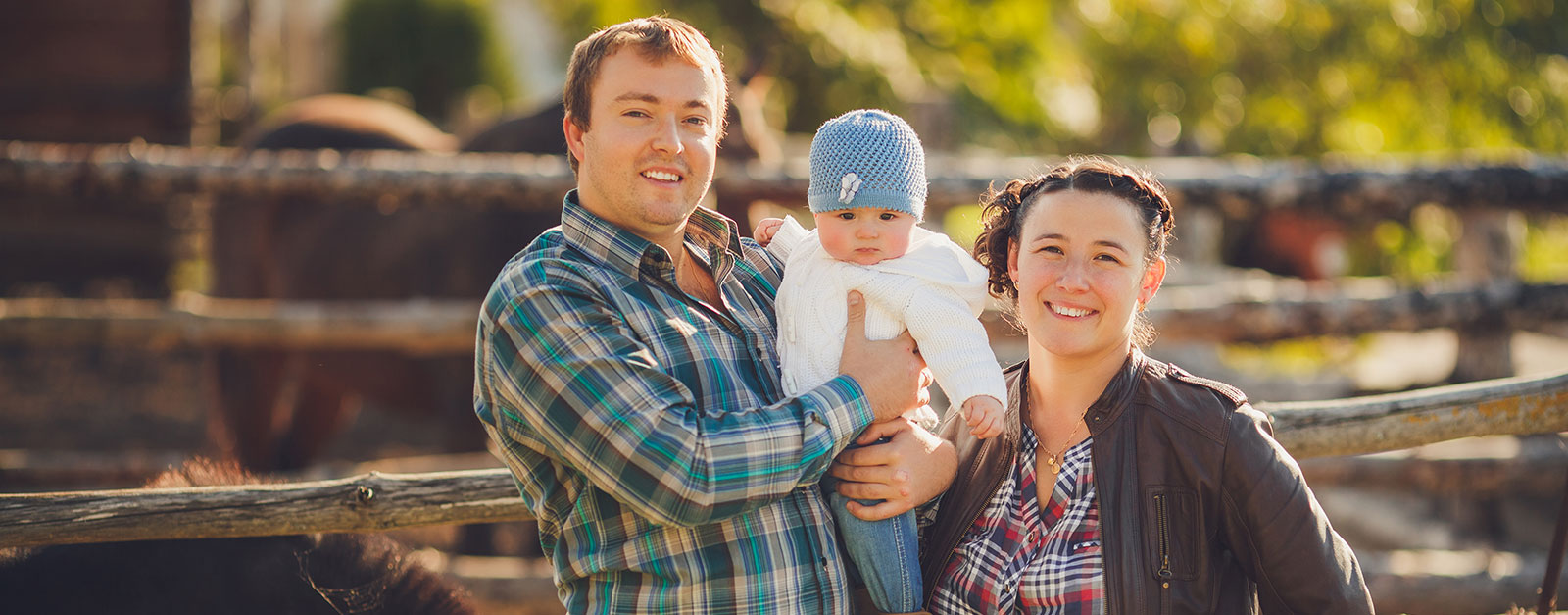 parents with their baby on a farm