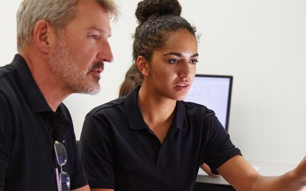 a man and woman working together at a computer