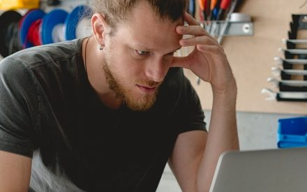 a stressed man looking at a computer in his work room