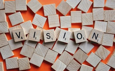 "the word ""vision"" spelled out in scrabble pieces"