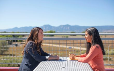 Two business women sitting at a table having a meeting outside